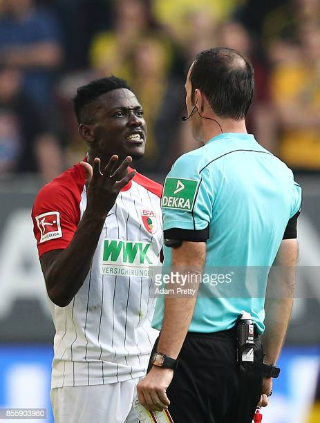 Daniel Opare of Augsburg argues with referee Marco Fritz during the Bundesliga match between FC Augsburg and Borussia Dortmund at WWKArena on...