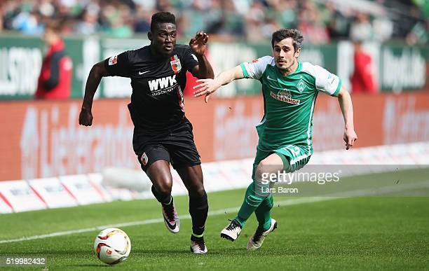 Daniel Opare of Augsburg is challenged by Fin Bartels of Bremen during the Bundesliga match between Werder Bremen and FC Augsburg at Weserstadion on...