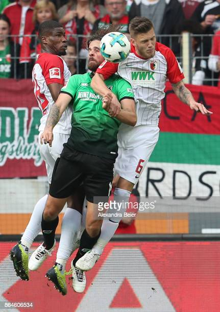 Daniel Opare of Augsburg Martin Harnik of Hannover and Jeffrey Gouweleeuw of Augsburg fight for the ball during the Bundesliga match between FC...