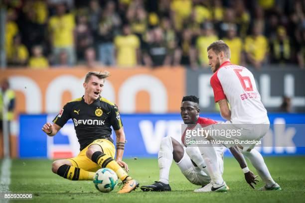 Daniel Opare of Augsburg tackles Maximilian Philipp of Borussia Dortmund during the Bundesliga match between FC Augsburg and Borussia Dortmund at...