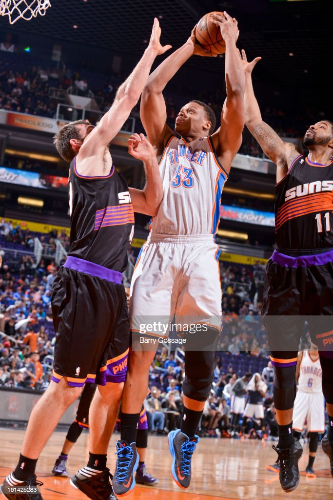Daniel Orton #33 of the Oklahoma City Thunder shoots in the lane against Luke Zeller #40 and Markieff Morris #11 of the Phoenix Suns on February 10, 2013 at U.S. Airways Center in Phoenix, Arizona.