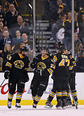 Daniel Paille is congratulated by Maxime Talbot and Torey Krug of the Boston Bruins after he scored a goal against the Detroit Red Wings in the...