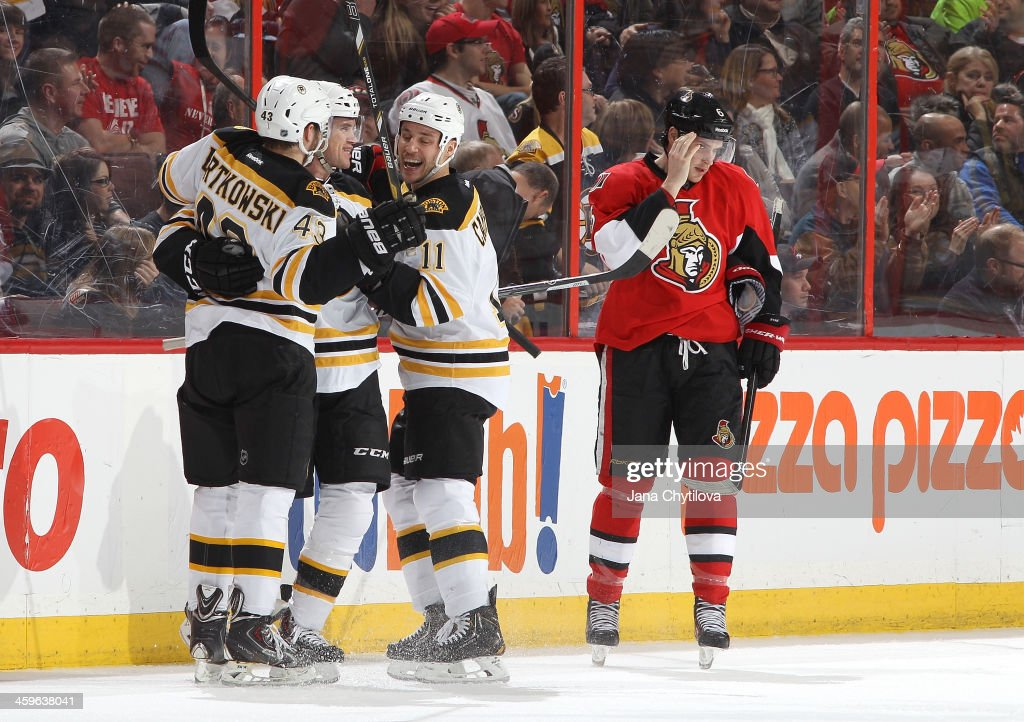 <a gi-track='captionPersonalityLinkClicked' href=/galleries/search?phrase=Daniel+Paille&family=editorial&specificpeople=706561 ng-click='$event.stopPropagation()'>Daniel Paille</a> #20 of the Boston Bruins celebrates his first-period goal with teammates <a gi-track='captionPersonalityLinkClicked' href=/galleries/search?phrase=Matt+Bartkowski&family=editorial&specificpeople=7203779 ng-click='$event.stopPropagation()'>Matt Bartkowski</a> #43 and <a gi-track='captionPersonalityLinkClicked' href=/galleries/search?phrase=Gregory+Campbell&family=editorial&specificpeople=640895 ng-click='$event.stopPropagation()'>Gregory Campbell</a> #11 as <a gi-track='captionPersonalityLinkClicked' href=/galleries/search?phrase=Bobby+Ryan+-+Ice+Hockey+Player&family=editorial&specificpeople=877359 ng-click='$event.stopPropagation()'>Bobby Ryan</a> #6 of the Ottawa Senators looks on during an NHL game at Canadian Tire Centre on December 28, 2013 in Ottawa, Ontario, Canada.