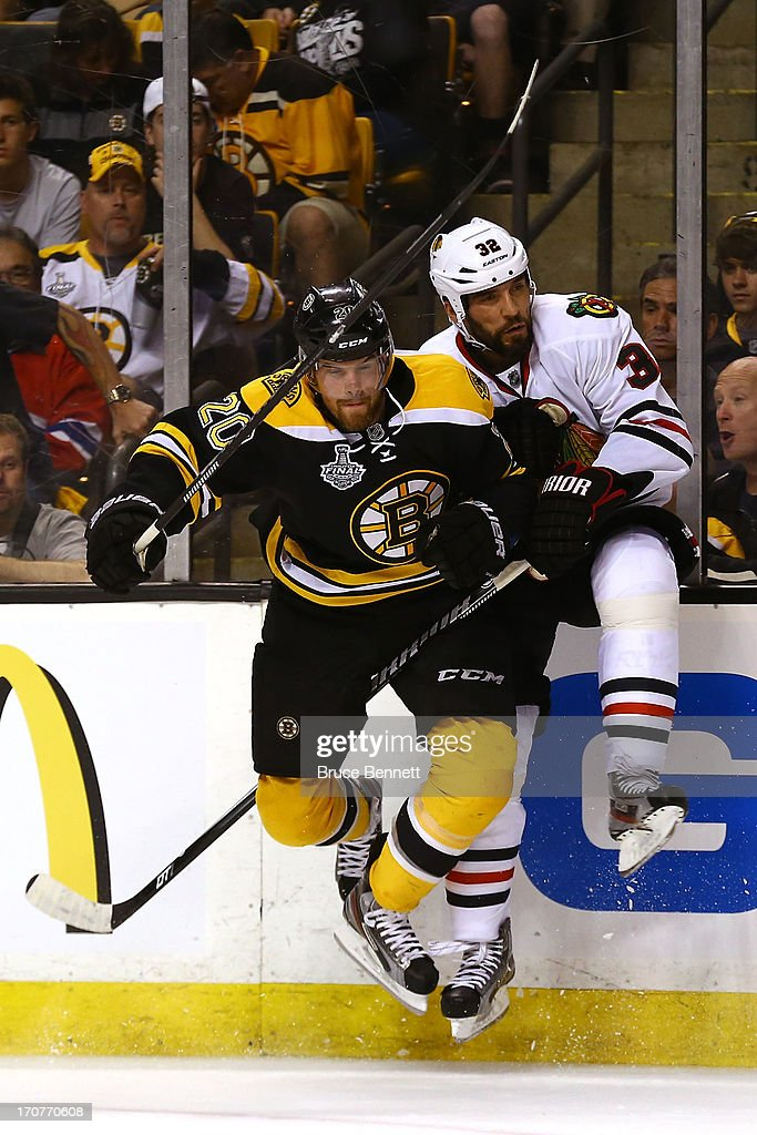 Daniel Paille of the Boston Bruins checks Michal Rozsival of the Chicago Blackhawks in Game Three of the 2013 NHL Stanley Cup Final at TD Garden on...