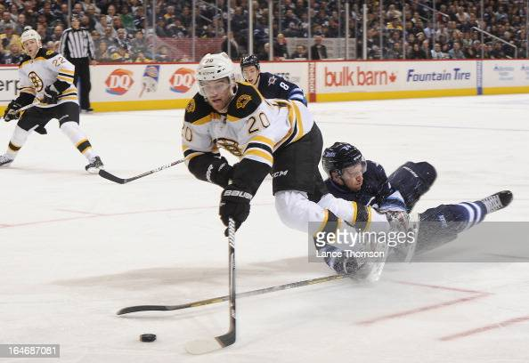 Daniel Paille of the Boston Bruins tries to play the puck as he trips over a fallen Grant Clitsome of the Winnipeg Jets during third period action at...