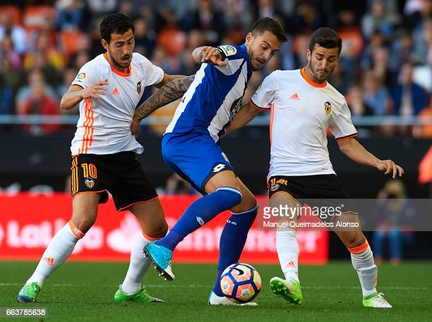 Daniel Parejo and Jose Luis Gaya of Valencia compete for the ball with Joselu Sanmartin of Deportivo de La Coruna during the La Liga match between...
