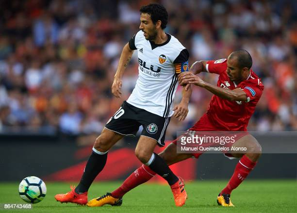 Daniel Parejo of Valencia is tackled by Guido Hernan Pizarro of Sevilla during the La Liga match between Valencia and Sevilla at Estadio Mestalla on...