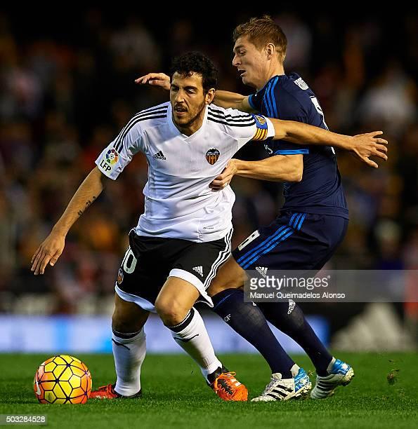 Daniel Parejo of Valencia is tackled by Toni Kroos of Real Madrid during the La Liga match between Valencia CF and Real Madrid CF at Estadi de...
