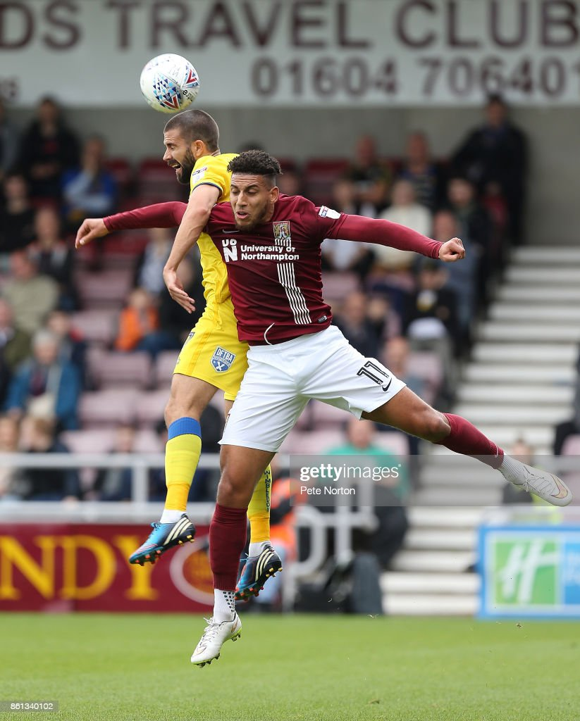 Daniel Powell of Northampton Town contests the ball with George Francomb of AFC Wimbledon during the Sky Bet League One match between Northampton Town and A.F.C. Wimbledon at Sixfields on October 14, 2017 in Northampton, England.