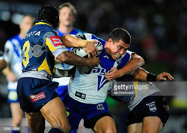 Daniel Rauicava of the Bulldogs is tackled by Ty Williams and Nick Slyney of the Cowboys during the round 24 NRL match between the North Queensland...
