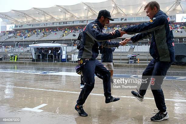 Daniel Ricciardo of Australia and Infiniti Red Bull Racing and Daniil Kvyat of Russia and Infiniti Red Bull Racing dance in the pit lane to entertain...
