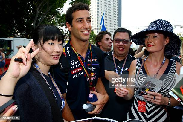 Daniel Ricciardo of Australia and Infiniti Red Bull Racing poses with fans as he arrives at the circuit before the Singapore Formula One Grand Prix...
