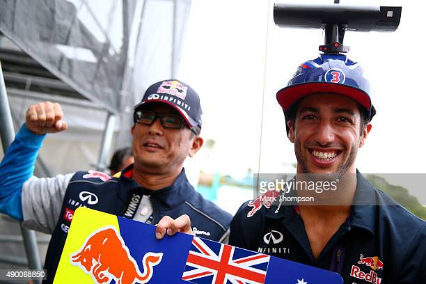Daniel Ricciardo of Australia and Infiniti Red Bull Racing poses with a fan in the fanzone after qualifying for the Formula One Grand Prix of Japan...