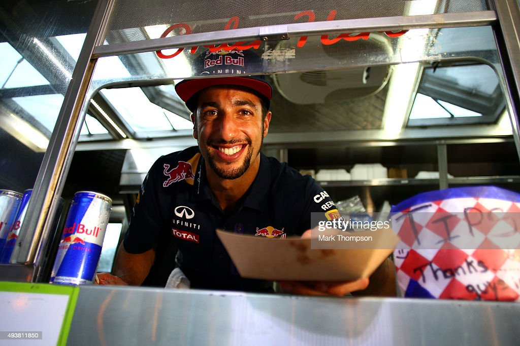 Daniel Ricciardo of Australia and Infiniti Red Bull Racing serves a customer at a food truck during previews to the United States Formula One Grand Prix near Austin University on October 22, 2015 in Austin, United States.