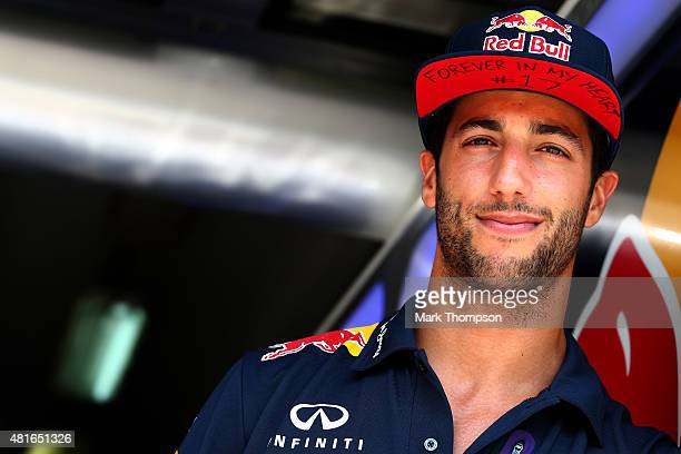Daniel Ricciardo of Australia and Infiniti Red Bull Racing stands in the garage wearing a cap displaying a message in memory of Jules Bianchi during...