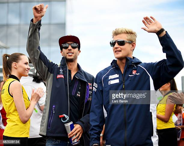 Daniel Ricciardo of Australia and Infiniti Red Bull Racing waves to the crowd next to Marcus Ericsson of Sweden and Sauber F1 during the drivers'...