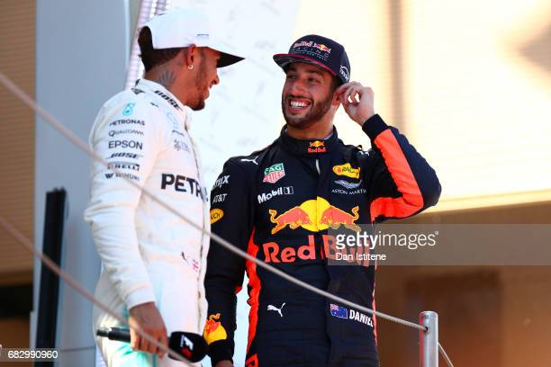 Daniel Ricciardo of Australia and Red Bull Racing and Lewis Hamilton of Great Britain and Mercedes GP talk on the podium during the Spanish Formula...