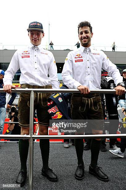 Daniel Ricciardo of Australia and Red Bull Racing and Max Verstappen of Netherlands and Red Bull Racing pose in lederhosen on the drivers parade...