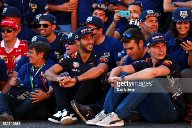 Daniel Ricciardo of Australia and Red Bull Racing and Max Verstappen of Netherlands and Red Bull Racing pose with Spanish Grand Prix volunteers on...