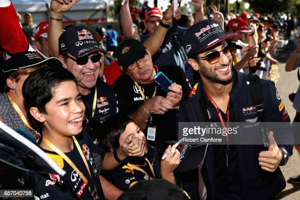 Daniel Ricciardo of Australia and Red Bull Racing arrives at the circuit and poses for a photo with fans during practice for the Australian Formula...