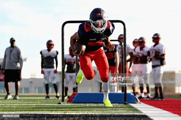 Daniel Ricciardo of Australia and Red Bull Racing at a training session with the Del Valle Cardinals High School Football Team during previews ahead...