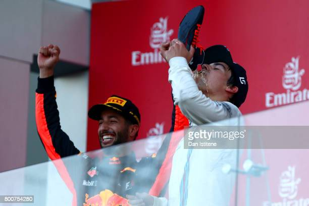 Daniel Ricciardo of Australia and Red Bull Racing celebrates on the podium as he offers a shoey to Lance Stroll of Canada and Williams after winning...