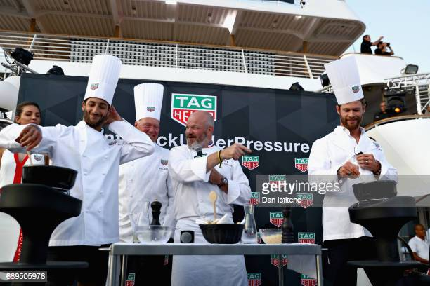 Daniel Ricciardo of Australia and Red Bull Racing Chef Philippe Etchebest and Actor Chris Hemsworth at the TAG Heuer Culinary Challenge on May 27...