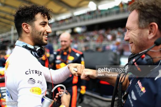 Daniel Ricciardo of Australia and Red Bull Racing fist bumps Red Bull Racing Team Principal Christian Horner on the grid before the Malaysia Formula...