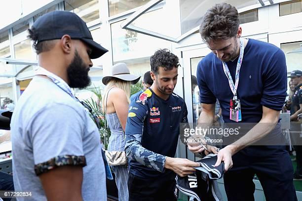 Daniel Ricciardo of Australia and Red Bull Racing gets his San Antonio Spurs jersey signed by San Antonio Spurs basketball player Pau Gasol during...