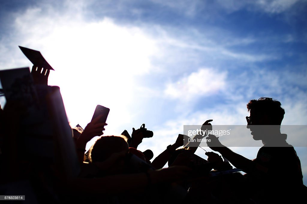 Daniel Ricciardo of Australia and Red Bull Racing signs autographs for fans in the pit lane during previews ahead of the Formula One Grand Prix of...