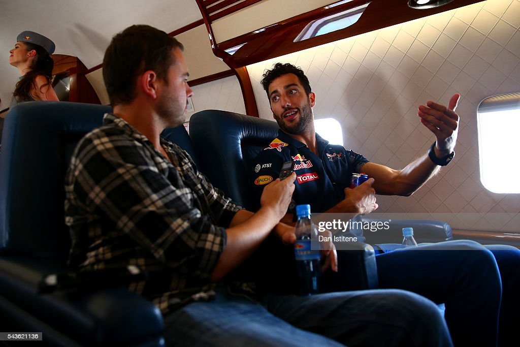 Daniel Ricciardo of Australia and Red Bull Racing speaks with a member of the media during a Red Bull Racing media flight to Hangar 7 on June 29, 2016 over Austria.