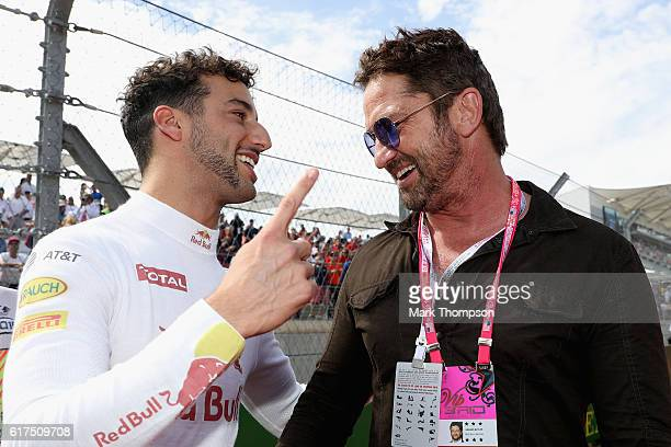 Daniel Ricciardo of Australia and Red Bull Racing talks with actor Gerard Butler on the grid before the United States Formula One Grand Prix at...