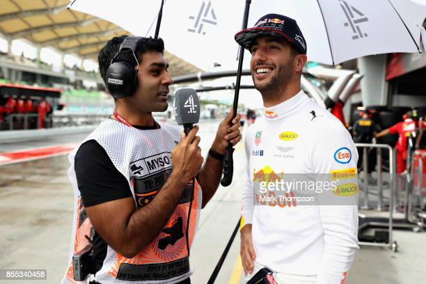 Daniel Ricciardo of Australia and Red Bull Racing talks with Karun Chandhok in the Pitlane during practice for the Malaysia Formula One Grand Prix at...