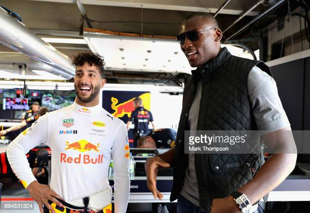 Daniel Ricciardo of Australia and Red Bull Racing talks with NBA player Bismack Biyombo of Congo in the Red Bull Racing garage during qualifying for...