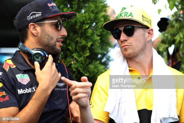 Daniel Ricciardo of Australia and Red Bull Racing talks with Nico Hulkenberg of Germany and Renault Sport F1 on the drivers parade before the Formula...