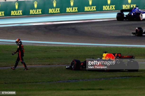 Daniel Ricciardo of Australia and Red Bull Racing walks from his car after retiring during the Abu Dhabi Formula One Grand Prix at Yas Marina Circuit...