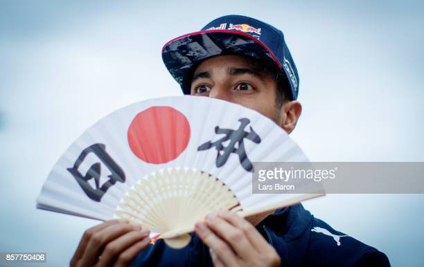 Daniel Ricciardo of Australia and Red Bull Racing with a Japanese fan during previews ahead of the Formula One Grand Prix of Japan at Suzuka Circuit...
