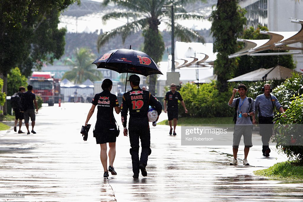 Daniel Ricciardo of Australia and Scuderia Toro Rosso walks through the paddock with press officer Marieluise Mammitzsch after being interviewed by the media following qualifying for the Malaysian Formula One Grand Prix at the Sepang Circuit on March 23, 2013 in Kuala Lumpur, Malaysia.