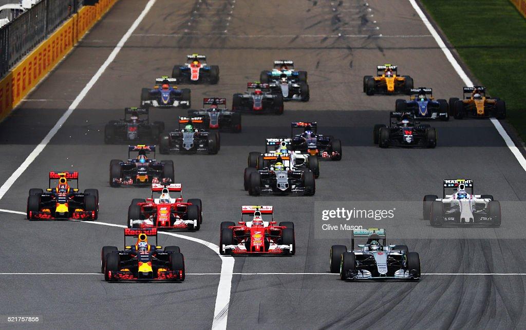 Daniel Ricciardo of Australia driving the Red Bull Racing Red BullTAG Heuer RB12 TAG Heuer races alongside Nico Rosberg of Germany driving the...