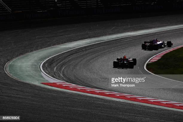 Daniel Ricciardo of Australia driving the Red Bull Racing Red BullTAG Heuer RB13 TAG Heuer follows Esteban Ocon of France driving the Sahara Force...