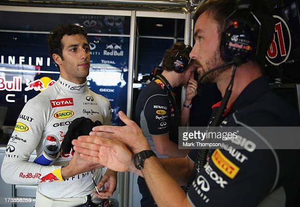 Daniel Ricciardo of Australia talks with his engineer Simon Rennie as he prepares to drive for the Infiniti Red Bull Racing team during the young...