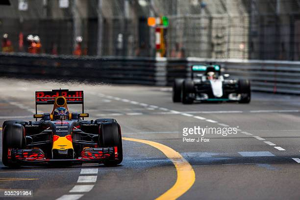 Daniel Ricciardo of Red Bull Racing and Australia exits the pitlane and loses the lead to Lewis Hamilton of Great Britain and Mercedes during the...