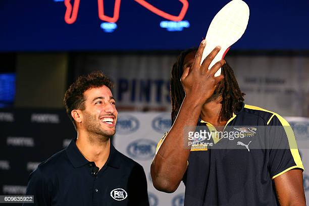 Daniel Ricciardo of Red Bull Racing watches Nic Naitanui of the West Coast Eagles AFL club pretend to do a 'shoey' at Crown Sports Bar on September...