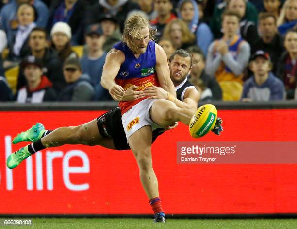 Daniel Rich of the Lions gets a kick away as Maverick Weller of the Saints lays a taclkle during the round three AFL match between the St Kilda...