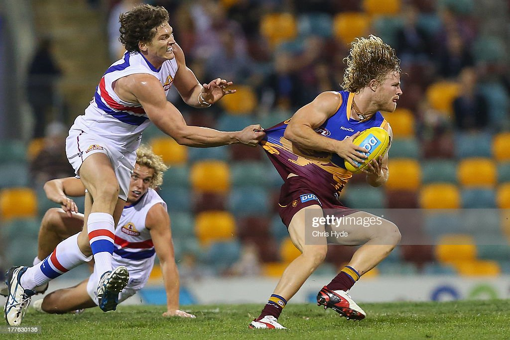 Daniel Rich of the Lions is tackled by WIll Minson of the Bulldogs during the round 22 AFL match between the Brisbane Lions and the Western Bulldogs at The Gabba on August 25, 2013 in Brisbane, Australia.