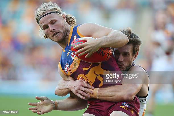 Daniel Rich of the Lions is tackled during the round 10 AFL match between the Brisbane Lions and the Hawthorn Hawks at The Gabba on May 28 2016 in...