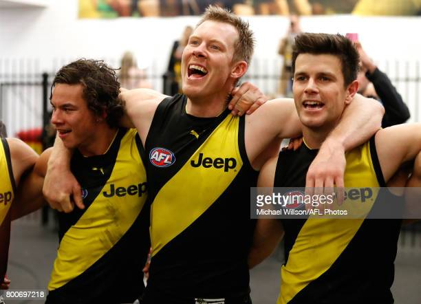 Daniel Rioli Jack Riewoldt and Trent Cotchin of the Tigers sing the team song during the 2017 AFL round 14 match between the Richmond Tigers and the...