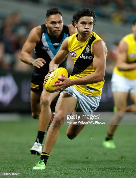 Daniel Rioli of the Tigers is chased by Jarman Impey of the Power during the 2017 AFL round 15 match between the Port Adelaide Power and the Richmond...