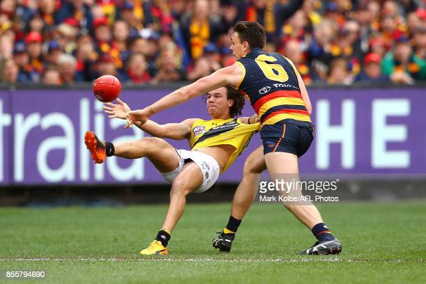 Daniel Rioli of the Tigers kicks as he is tackled by Jake Lever of the Crows during the 2017 AFL Grand Final match between the Adelaide Crows and the...