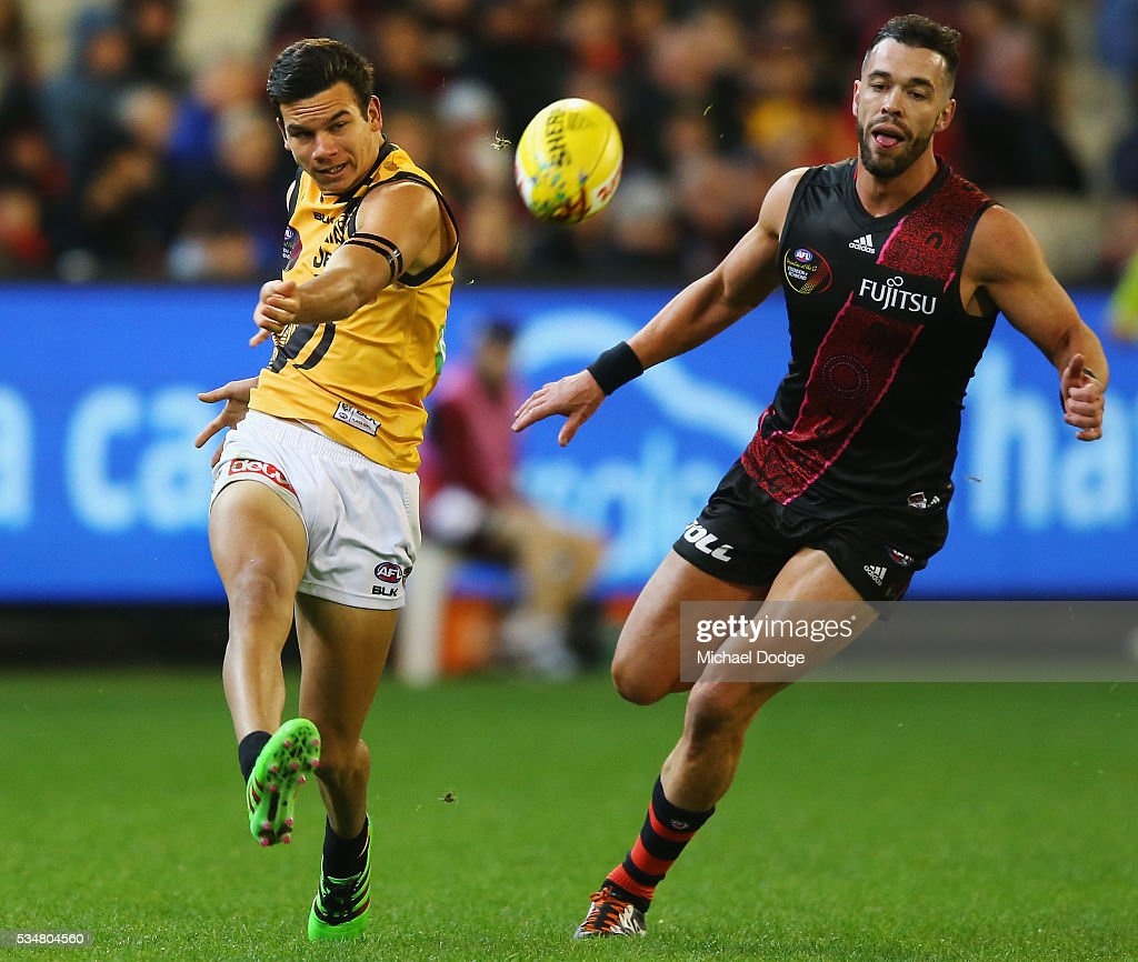 Daniel Rioli of the Tigers kicks the ball away from Ryan Crowley of the Bombers during the round 10 AFL match between the Essendon Bombers and the Richmond Tigers at Melbourne Cricket Ground on May 28, 2016 in Melbourne, Australia.